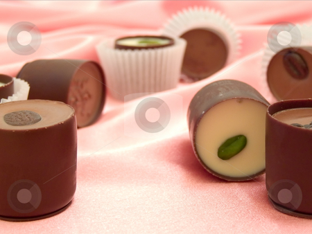 Chocolat sweets stock photo, Different chocolate sweets at the pink silk by Sergej Razvodovskij