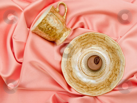 Saucer and cup with chocolate stock photo, Saucer and cup with chocolate on the pink silk by Sergej Razvodovskij