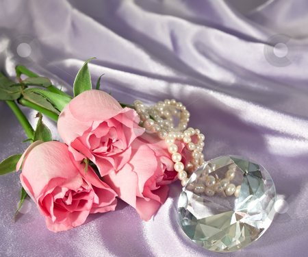 Rosebuds and diamond and pearls stock photo, Three pink rosebuds with pearls and a diamond lying on lilac satin by Norma Cornes