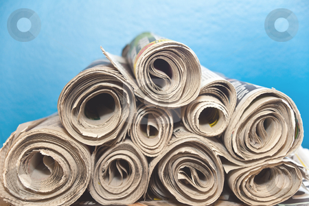 Rolled upNewspapers stock photo, A stack of old rolledup newspapers with a blue background by Norma Cornes