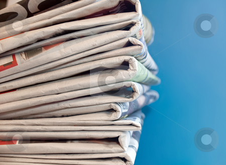 Newspapers stock photo, A stack of old newspapers with a blue background by Norma Cornes