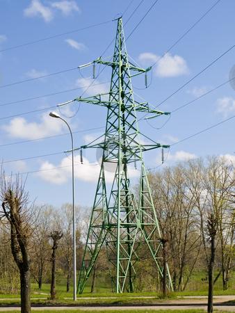 Electricity tower in trees stock photo, Single electricity tower in trees against the blue sky by Sergej Razvodovskij