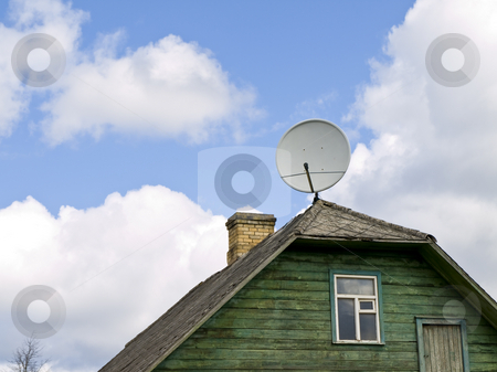 Satellite dish stock photo, Satellite dish at the housetop against the blue sky and clouds by Sergej Razvodovskij