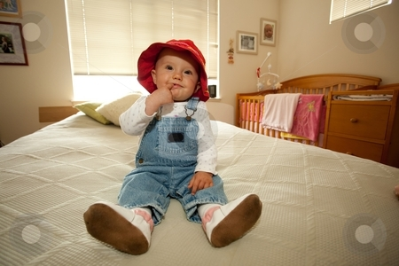 Red Hat stock photo, Cute little caucasian baby girl wearing red hat and sitting on a bed. by Mariusz Jurgielewicz