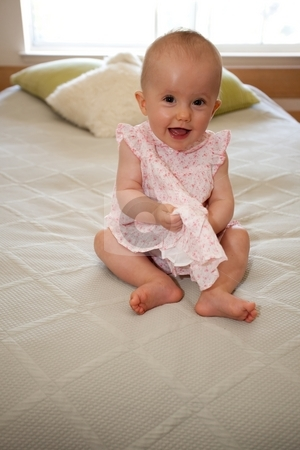 Pink Dress stock photo, Cute little caucasian baby girl wearing pink dress and sitting on a bed. by Mariusz Jurgielewicz