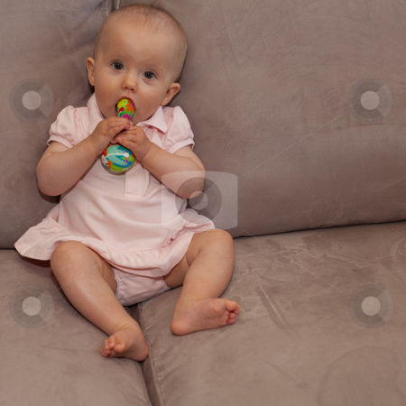 Playing on a sofa stock photo, Little caucasian baby girl sitting on a sofa. by Mariusz Jurgielewicz