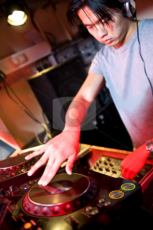 Disc Jockey stock photo, Disc jockey at work behind a turn table in a discotheque by Corepics VOF