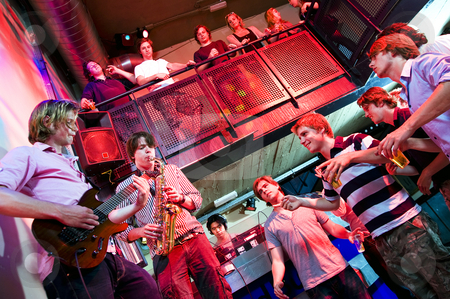 Disco gig stock photo, Musicians on Guitar and Saxophone, accompanied by a DJ, performing in a nightclub by Corepics VOF