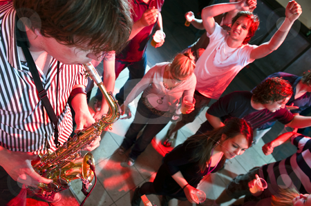 Saxophonist stock photo, Saxophonist playing in a nightclub, with dancing people in the background by Corepics VOF