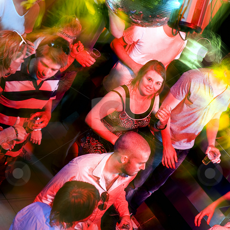 Dance floor smile stock photo, Girl smiling at the camera on a crowdy dance floor in a discotheque by Corepics VOF