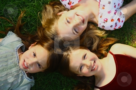 Three girls lying on grass stock photo, Three girls lying on grass by Gregory Dean