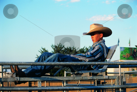 Little cowboy stock photo, Kid sitting in chair watching a rodeo by Andreas Brenner