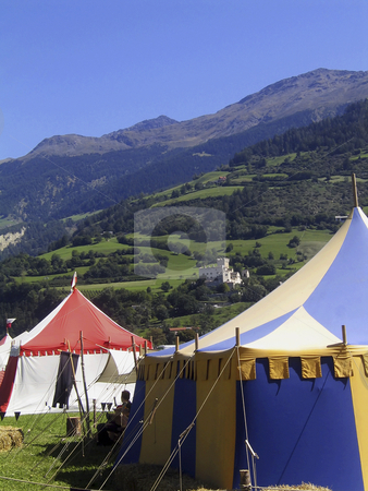 Medieval tents stock photo, The reconstruction of a Medieval camp at a renaissance festival with Coira Castle (Italy) in the background by Alessandro Rizzolli