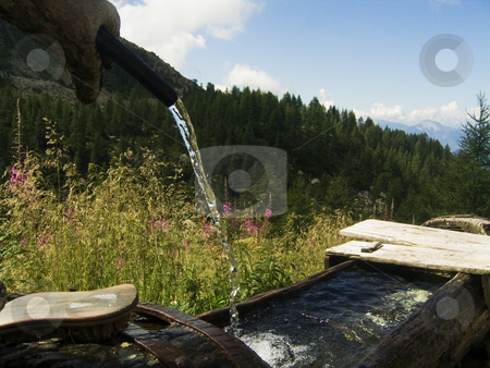 Fresh water in the mountains stock photo, Water falling from an old fountain in the Italian Alps by Alessandro Rizzolli