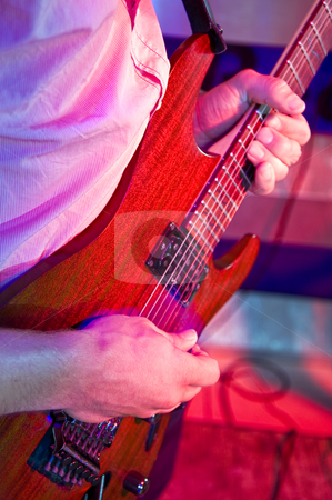 Guitarist stock photo, Looking over the shoulder of a guitarist at his hands, on a stage in a discotheque by Corepics VOF