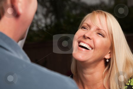 Blonde Woman Socializing with Friend stock photo, Attractive Blonde Woman Socializing with Man at an Evening Gathering. by Andy Dean