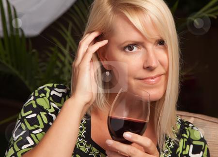 Beautiful Blonde Woman Enjoying Wine stock photo, Beautiful Blonde Woman Smiling at an Evening Social Gathering Tasting Wine. by Andy Dean