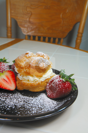 Creampuff And Strawberries stock photo, Cream pastry and freash strawberries on a black dessert plate dusted with white powdered sugar by Lynn Bendickson