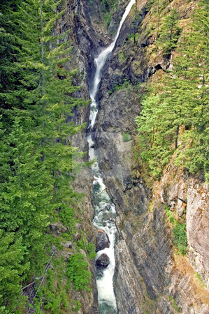 Long Steep Waterfall stock photo, This narrow but long waterfall is through steep crags in the mountain in this stunning landscape scene. by Valerie Garner
