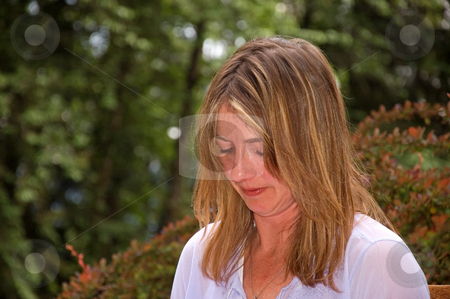 Natural Looking Caucasian Woman stock photo, This natural looking Caucasian woman in her late thirties is looking down working on something in a garden scene. by Valerie Garner