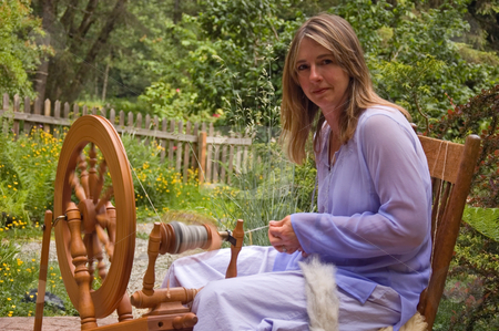 Woman Spinning Yarn stock photo, This Caucasian woman is spinning wool on a spinning wheel into homespun crafted yarn as an artisan in action. by Valerie Garner