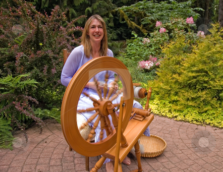 Woman Making Homespun Yarn stock photo, This artisan woman is hand crafting wool into homespun yard using a spinning wheel in a beautiful garden setting. by Valerie Garner