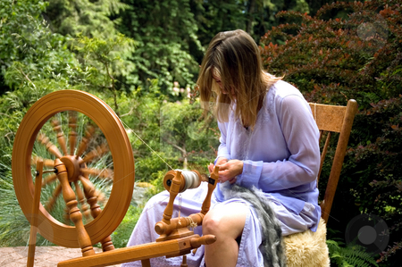 Woman in Action Making Yarn stock photo, This woman in action is making homemade yarn with a spinning wheel from raw wool for a unique hand crafted work.  Shot in a beautiful garden setting. by Valerie Garner