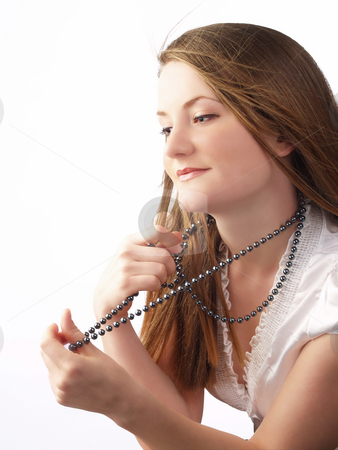 Young Woman in white blouse holding bead necklace stock photo, Young woman holding string of beads necklace by Jeff Cleveland