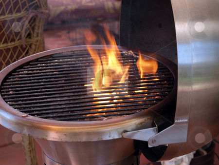 Flames coming up in silver barbeque grill stock photo, Silver barbeque grill with flames coming up by Jeff Cleveland