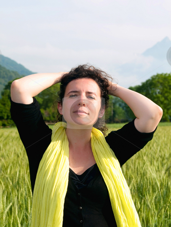 Woman in barley field stock photo, Photo of an attractive french woman wearing a yellow scarf standing in a green barley field with mountains in the background by Laurent Dambies