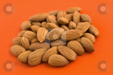 Almonds, orange background. stock photo, Group of almond kernels on orange background. by Pablo Caridad