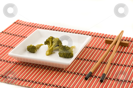 Broccolli dish with chinese chopsticks stock photo, Broccolli dish with chinese chopsticks, on bamboo mat, studio shot by Pablo Caridad