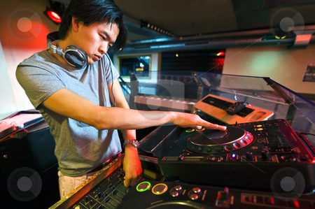 DJ in the Mix stock photo, DJ working on the faders and turntables during his act in a club by Corepics VOF