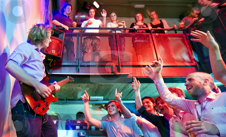 Crowd going wild stock photo, Crowd going wild during a live performance of a guitarist in a club by Corepics VOF