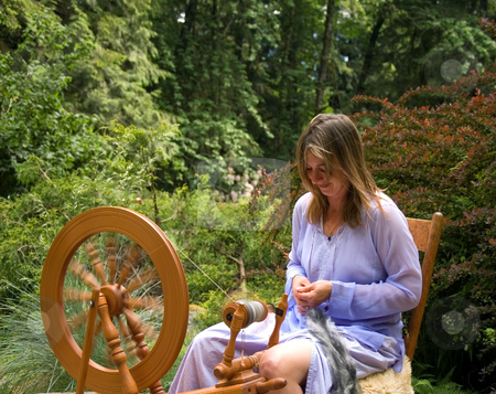 Entrepreneurial Woman at Her Business Product stock photo, This woman in action is making homemade yarn with a spinning wheel from raw wool for a unique hand crafted work. Shot in a beautiful garden setting. by Valerie Garner