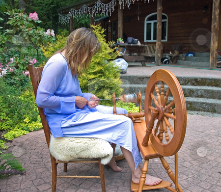 Self Employed Business Woman Working stock photo, This artisan woman is hand crafting wool into homespun yard using a spinning wheel at her home in which she is self employed in this as a business. by Valerie Garner