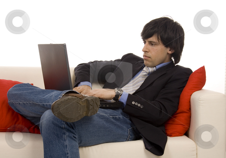 Relax on the sofa stock photo, Casual young man on a sofa with laptop by Marc Torrell