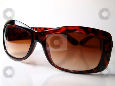 Brown sunglasses stock photo, Luxury shades placed on a white background by Arve Bettum