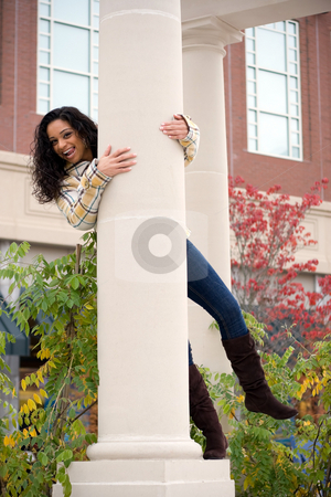 Goofing Around stock photo, A young woman playing around on a large pillar outside. by Todd Arena