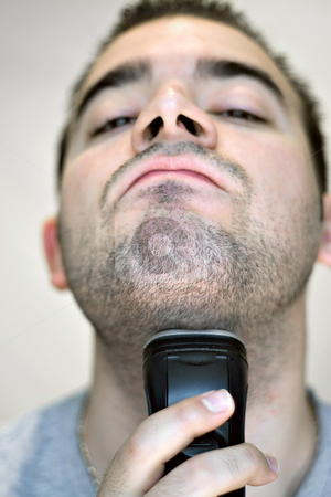 Man Shaving stock photo, A closeup of a young man shaving his beard off with an electric shaver. Shallow depth of field. by Todd Arena