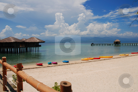 Kayaks on beautiful beach stock photo, Kayaks and cottages at the beach by Alvin Gacusan