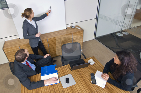 Business presentation stock photo, Three young business associates in a meeting, one presenting a theory in front of a white screen. by Corepics VOF