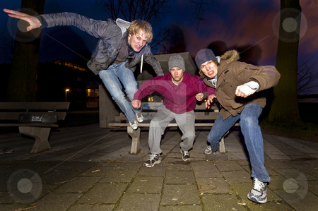 Urban aggression stock photo, Three juveniles leaping off a park bench, ready for a fight by Corepics VOF
