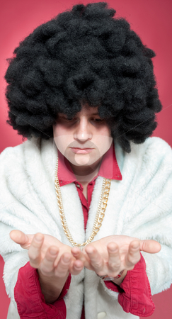 Pimp stock photo, Pimp looking at his hands wearing a fur coat and golden chain. by Corepics VOF