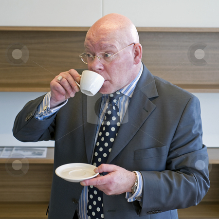 Sipping coffee stock photo, A senior manager sipping coffee and looking up from behind his cup at what is going on around him by Corepics VOF
