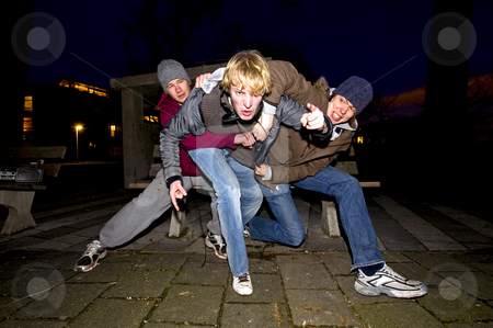 Urban aggression stock photo, A very aggressive and angry man trying to free himself from two of his friends who are restraining him from attacking by Corepics VOF