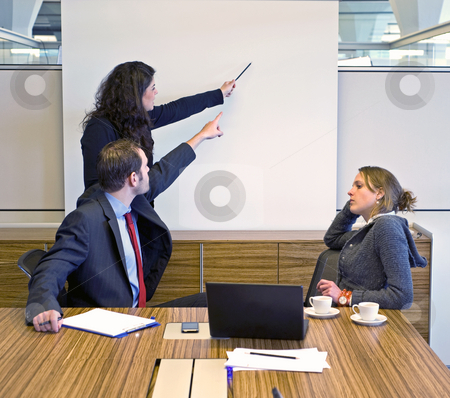 Disagreeing stock photo, Two colleagues pointing at a presentation screen, trying to convince a bored looking businesswoman by Corepics VOF