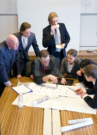 Design Team Meeting stock photo, Seven people gathering around the architectural plans, discussing the design in an office cubicle by Corepics VOF