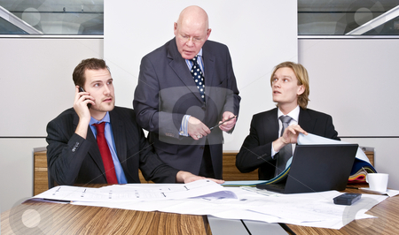 Design meeting stock photo, Two junior architects and a senior manager going over the final details of a design in a cubicle by Corepics VOF