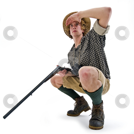 Searching Hunter stock photo, A crouching hunter, with a gun in his hand, searching for his prey by Corepics VOF